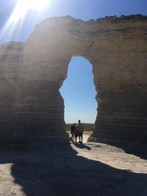 Young family framed by rock arch at Monument Rocks National Natural Landmark