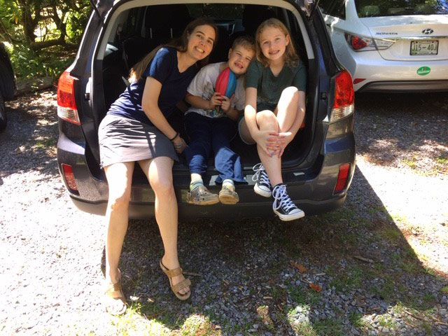 Young family with packed car ready to head out West on a summer road trip