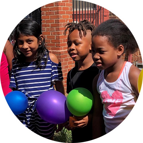 Three kids from the Washington DC Jubilee Housing early start summer program with their balloon-powered Mars landers