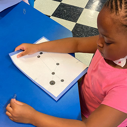 Young child making constellations in summer program