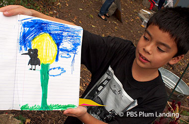 young boy holding up a drawing of a tree, the sky, and a bird