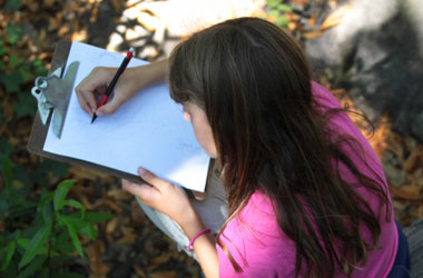 photo of girl writing on clipboard