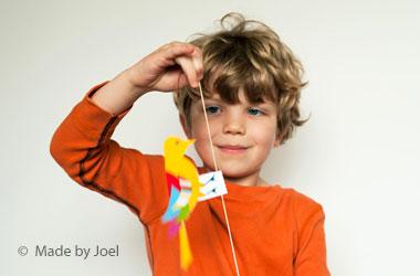 boy holding a paper bird on a string