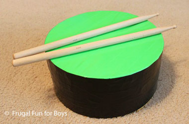 photo of a homemade black and green drum and two drumsticks