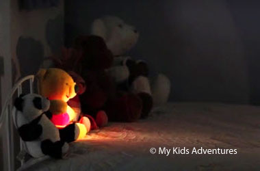 a row of stuffed animals lit by a flashlight