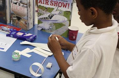 photo of a boy assembling a loopy plane