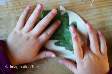child pressing leaf into clay