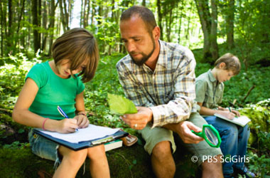 two children writing on clipboards and man showing one of them a leaf, they are in the woods