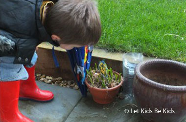 young boy checking a homemade rain gauge