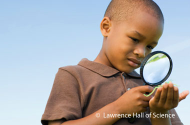 boy looking a something in his palm through a magnifying glass