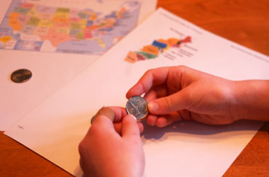 a US map and hands holding a quarter