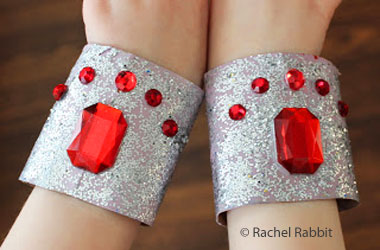 photo of child wearing silver cuffs covered in red stones