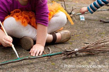 Child painting the handle of a bunch of sticks made to look like a broom.