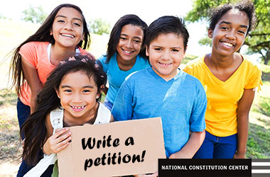 photo of five children holding a cardboard sign that says write a petition