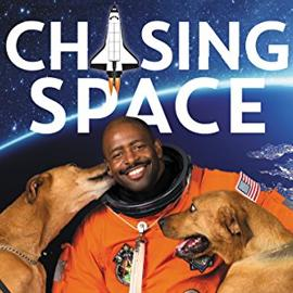 photo cover of Chasing Space showing an astronaut in his space suit and two dogs
