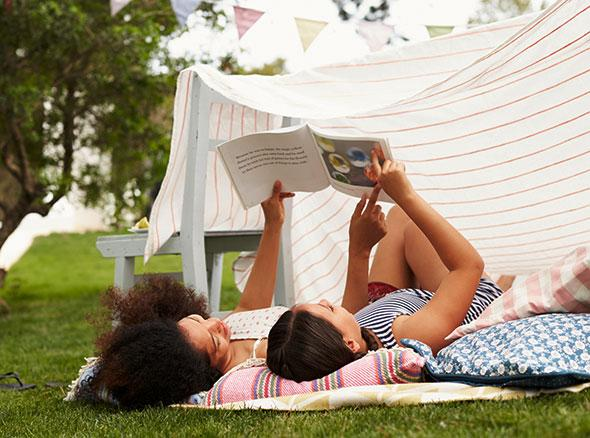 a mother and daughter lying on the ground reading a book with a sheet tented over them