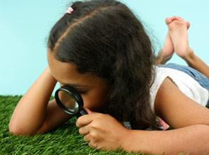 girl looking through magnifying glass at the ground
