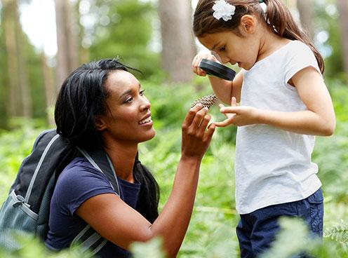 a woman holds up a pinecone which a young girl examines with a magnifying glass