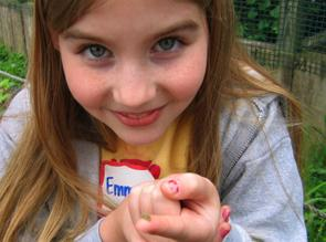 young girl hold bug on her fingertip.