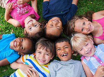 photo of seven children lying on the ground with their heads together in a circle
