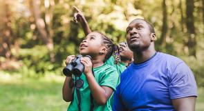 Black father with two young kids birdwatching