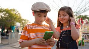 Two kid listening to audiobooks outside on a smart phone