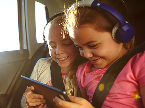 two you girls wearing headphones and looking at a tablet device while in a car