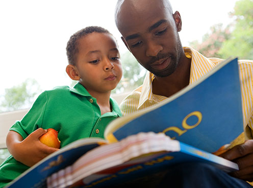upshot of man reading to a child while outside
