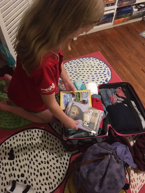 Young girl packing books for summer road trip to National Parks in Colorado